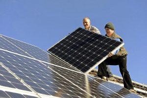 Zwei Arbeiter bei der Montage einer Photovoltaik-Anlage auf einem Hausdach